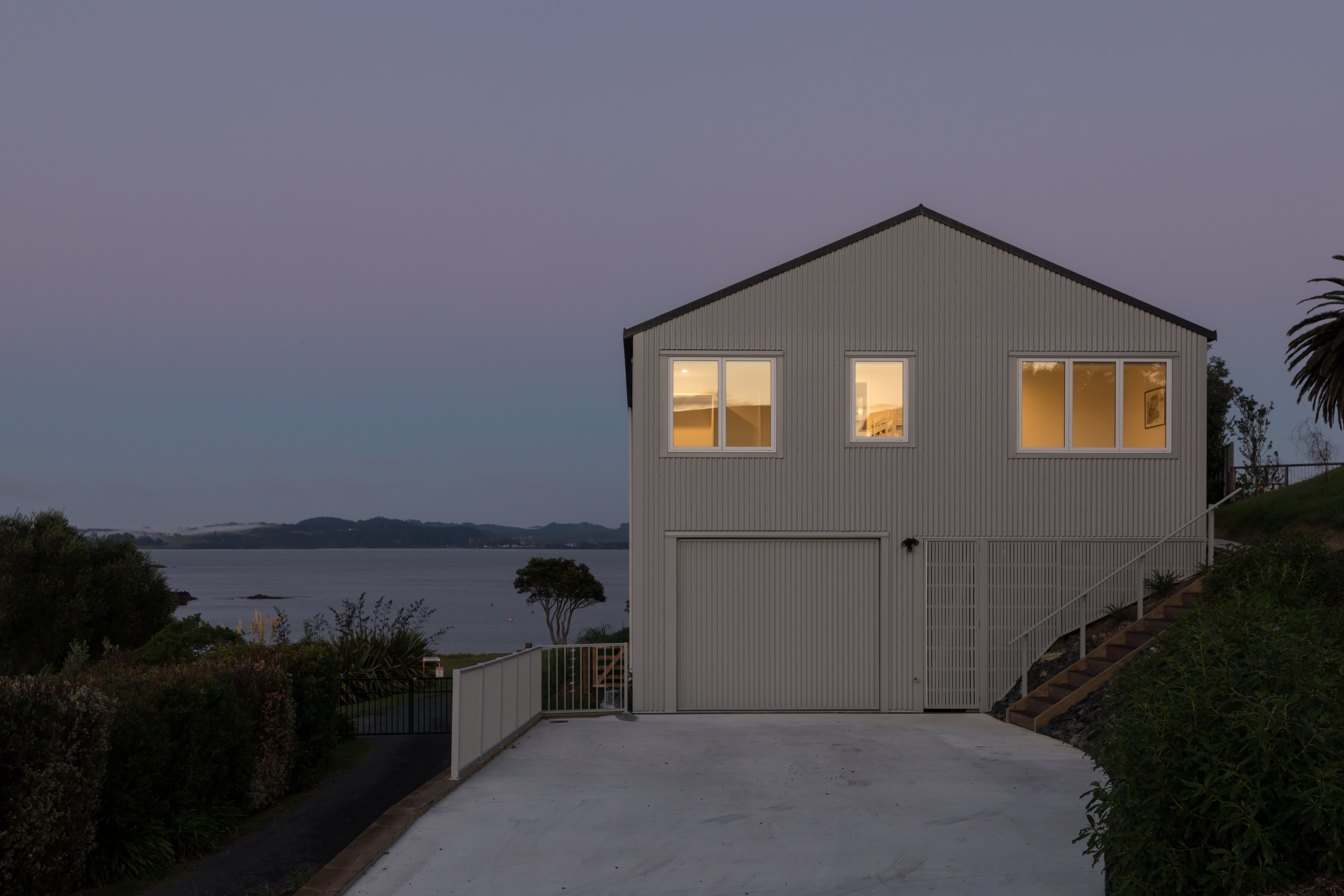 Dusk light shows this new gable-roofed beach house with sea views.